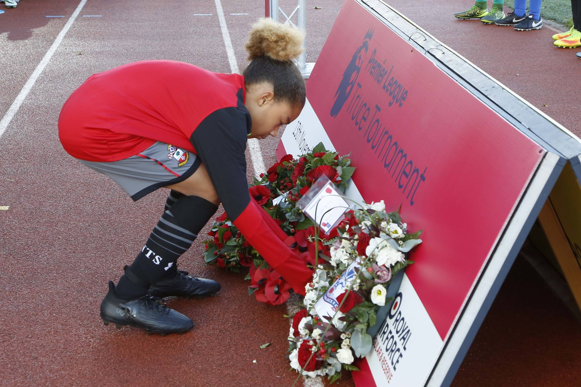 A Saints youngster lays a wreath of remembrance